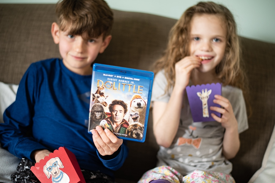 two kids sitting on a sofa eating snacks with the Dolittle DVD