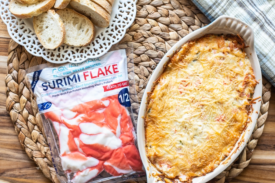a bag of aquamar surimi flakes sitting next to a dish with hot crab dip and a plate of sliced bread