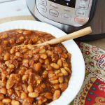 a bowl of baked beans sitting in front of a pressure cooker on a table with a wooden spoon