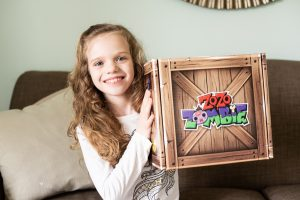 a girl holding up a box that says zo zo zombie on it
