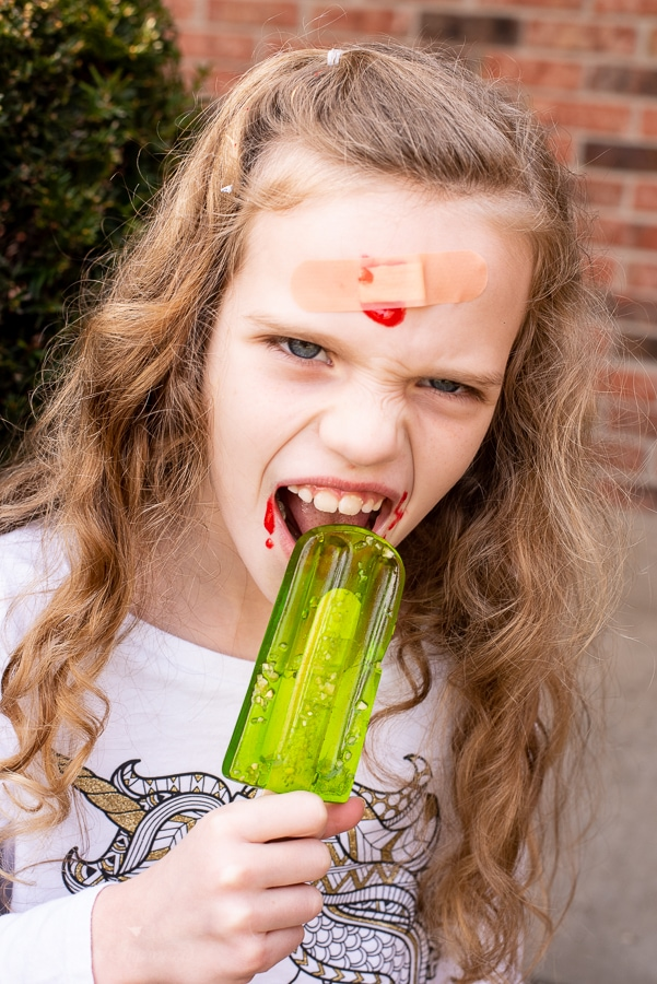 a girl with candy blood and a band aid on her face eating a lolipop