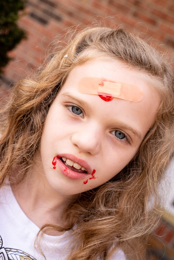 a girl pretending to be a zombie with candy blood on her face