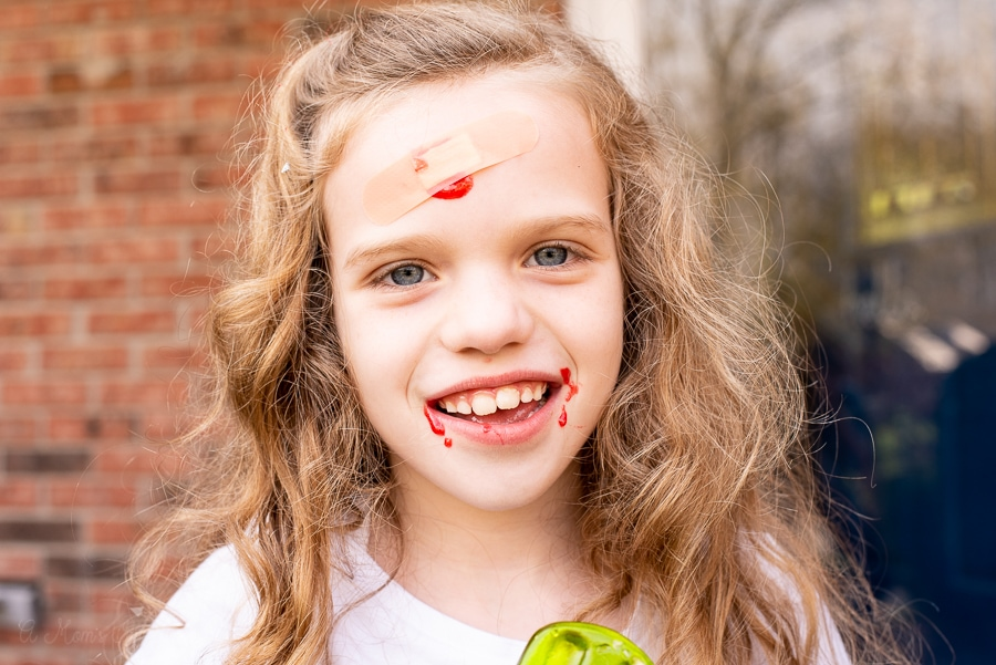 a girl with candy blood and a band aid on her face, smiling