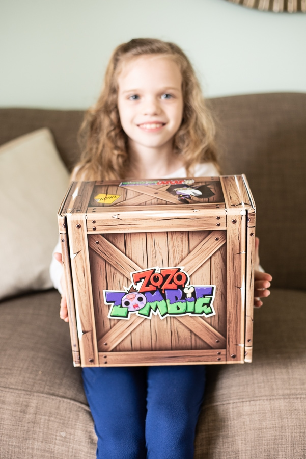 a girl sitting on the sofa with a zo zo zombie box on her lap