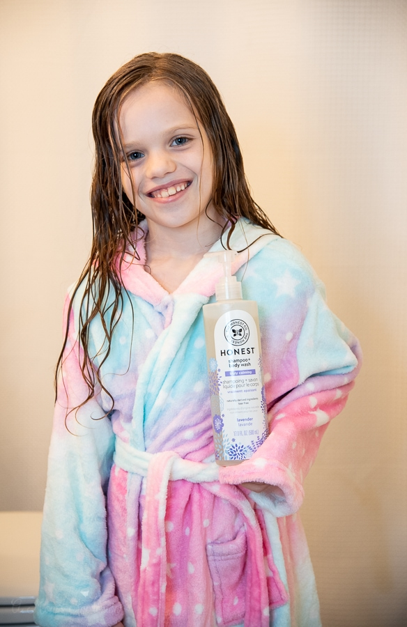 a girl smiling and holding a body wash bottle in her robe