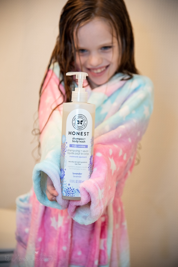 a girl holding out a bottle of shampoo and body wash