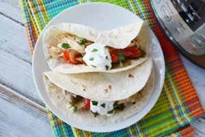 Instant Pot Chicken Fajitas served next to a pressure cooker for dinner.