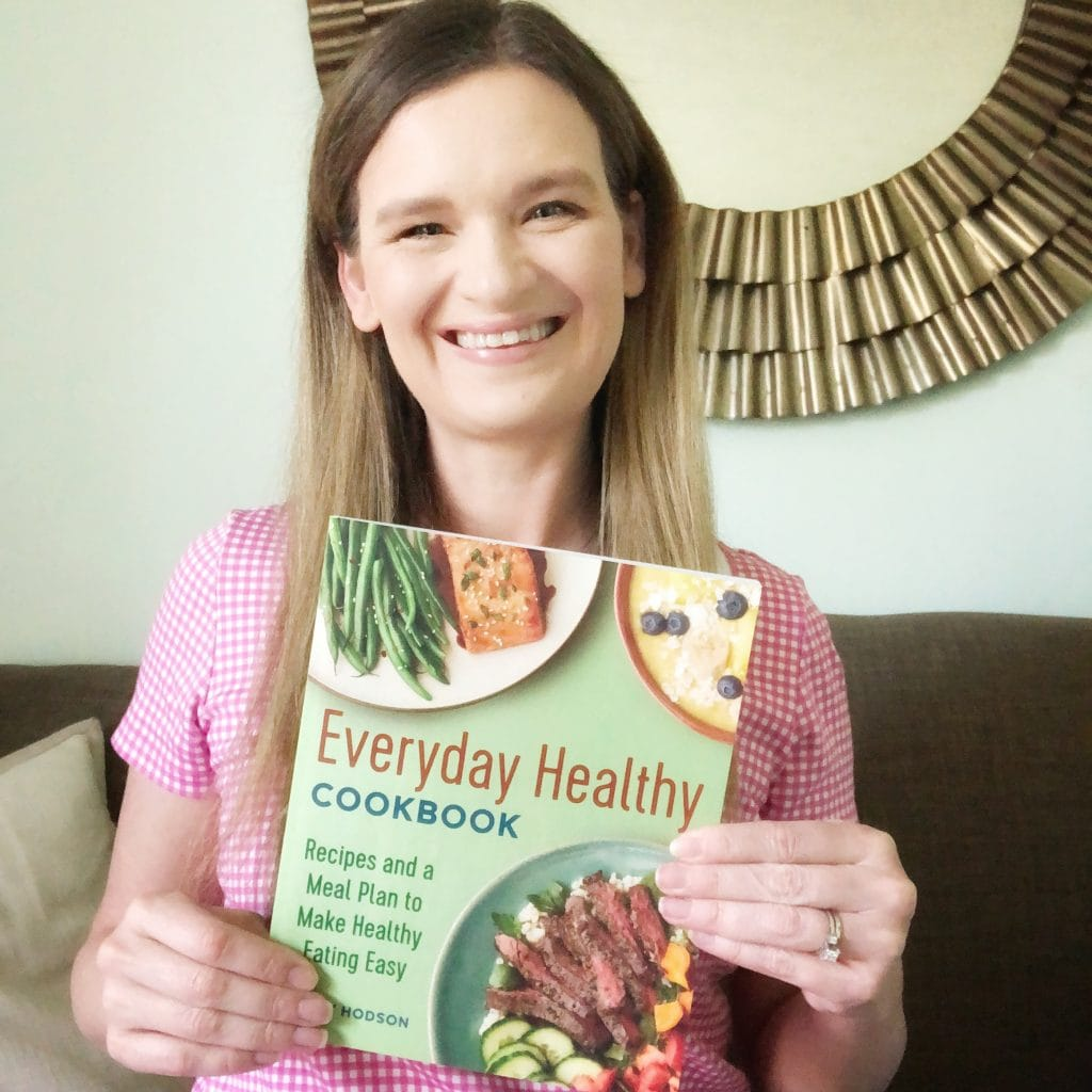 a girl holding a cookbook that she wrote