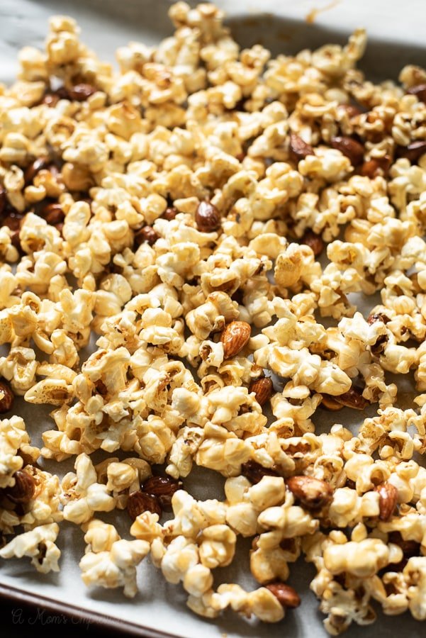 a pan of caramel popcorn with almonds drying out