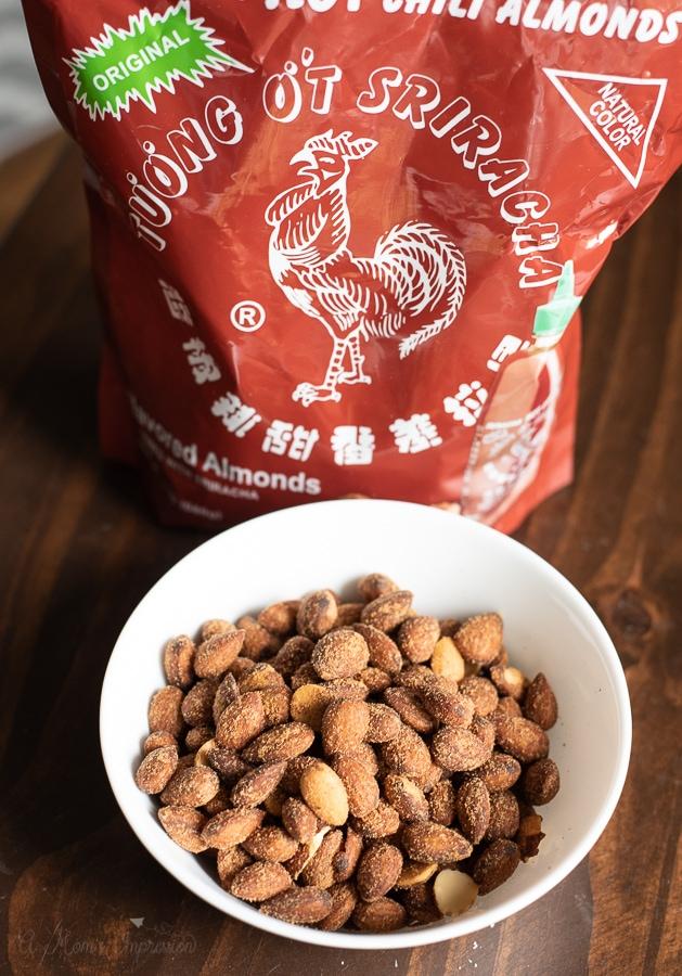 a bag of sriracha almonds behind a bowl of the same