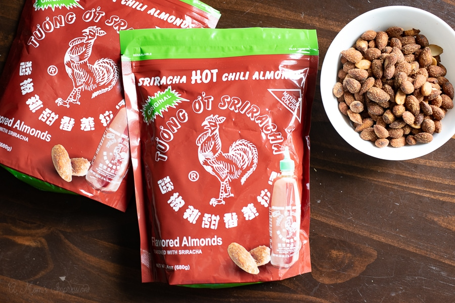 2 bags of sriracha almonds on a table next to a bowl of spicy almonds