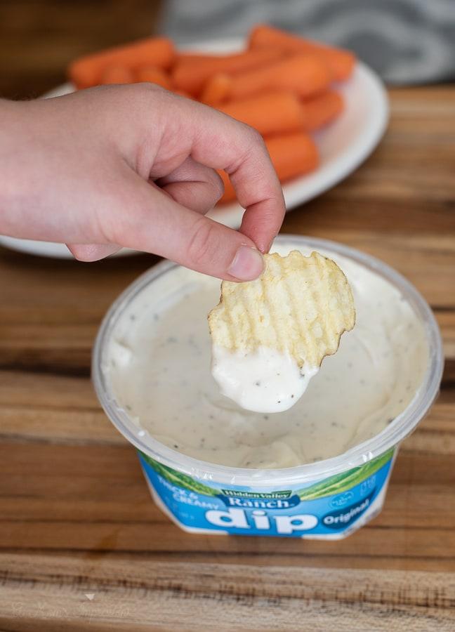 a person dipping a chip into Hidden Valley Ranch Dip