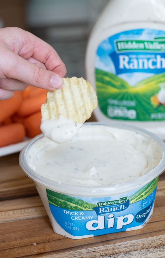 a person pouring Hidden Valley ranch dressing on chips and vegetables
