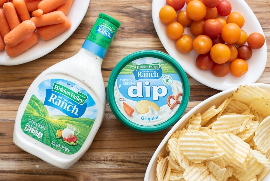 Hidden Valley Ranch products sitting on a table with carrots, tomatoes and chips