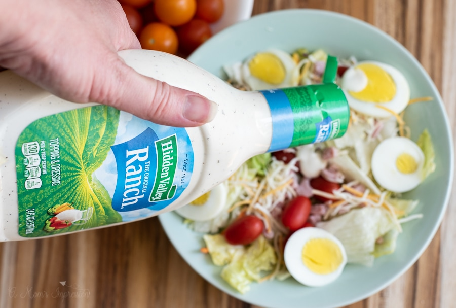 a person pouring Hidden Valley ranch dressing on a salad