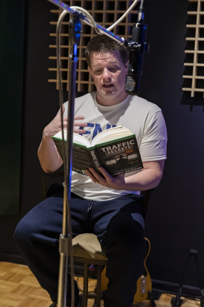 A picture of Russell Brunson reading his book