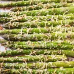 Oven roasted asparagus laying on a baking sheet