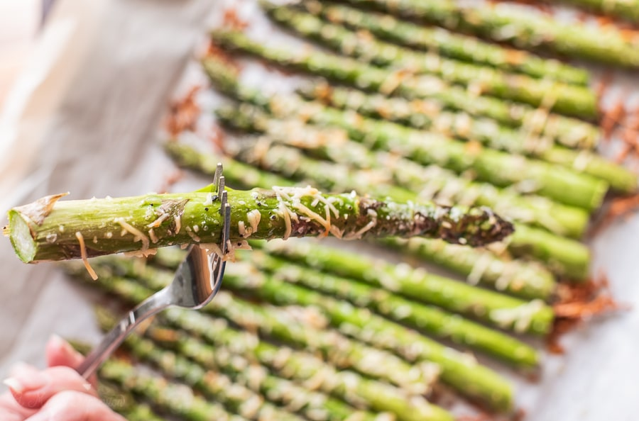an asparagus spear on a fork in front of a pan of roasted garlic asparagus