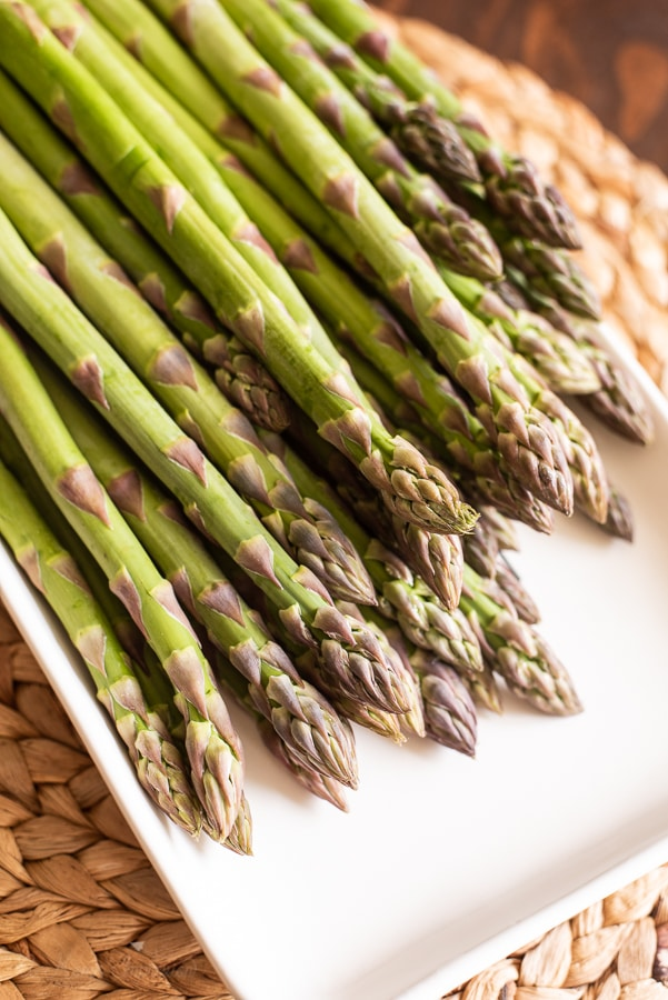 a closeup of a plate of raw asparagus stems