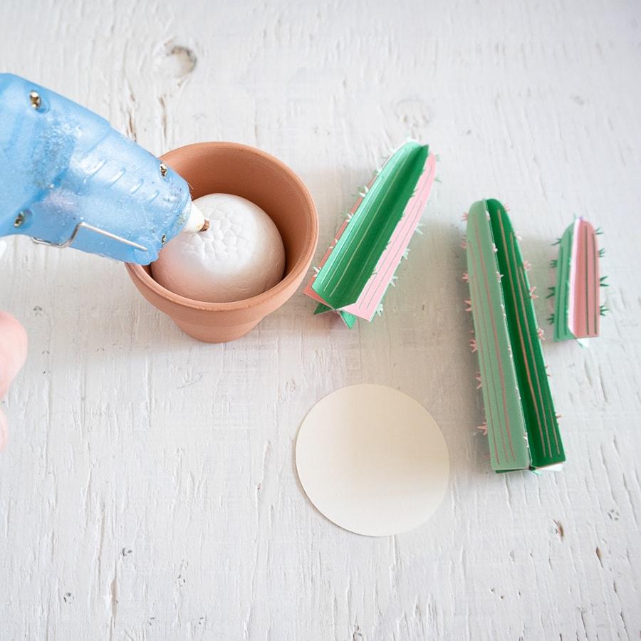 a person gluing a foam ball into a pot