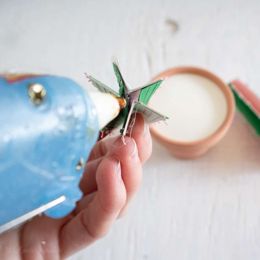 a person putting hot glue onto a paper flower