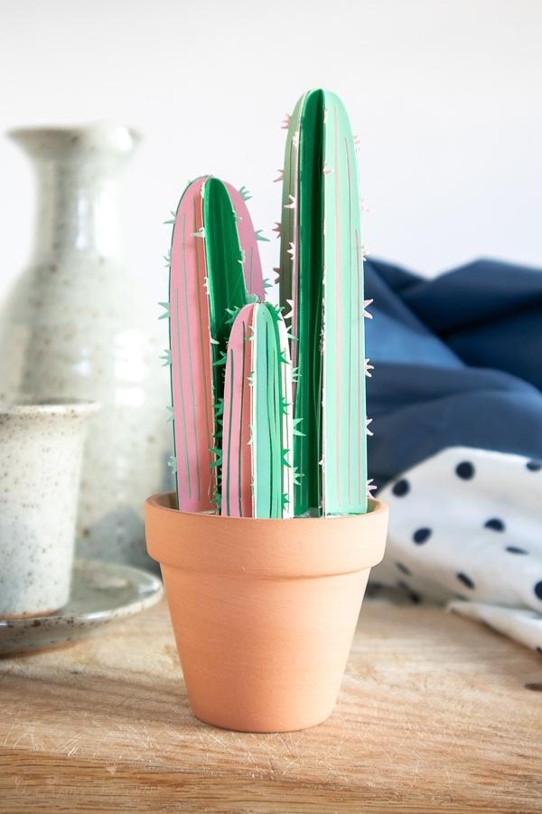 a cricut cactus craft in a pot next to a bed
