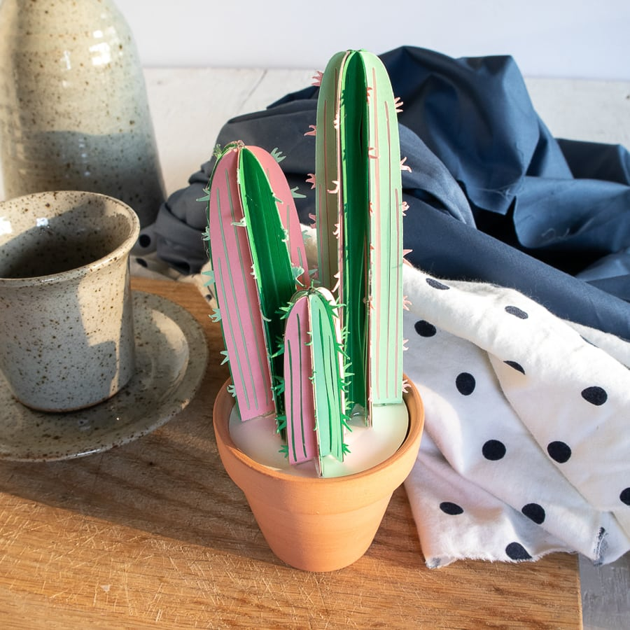 a paper cactus craft sitting on a bedside table