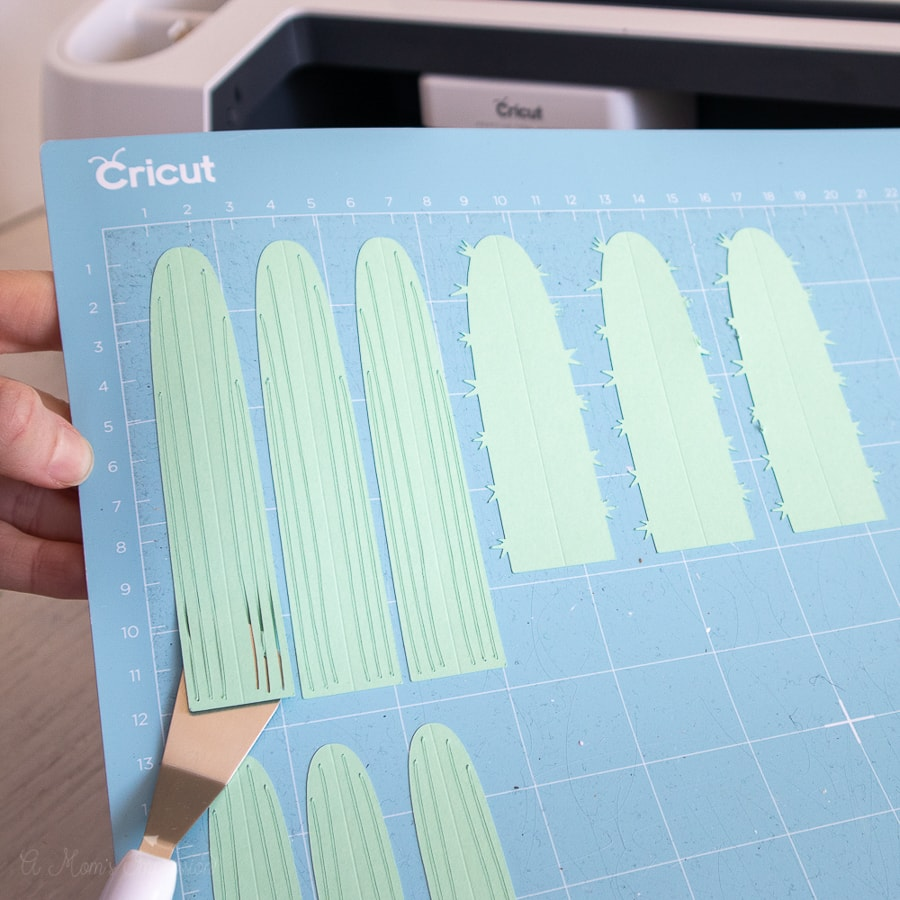 a person using a spatula tool to remove paper from a cricut cutting mat