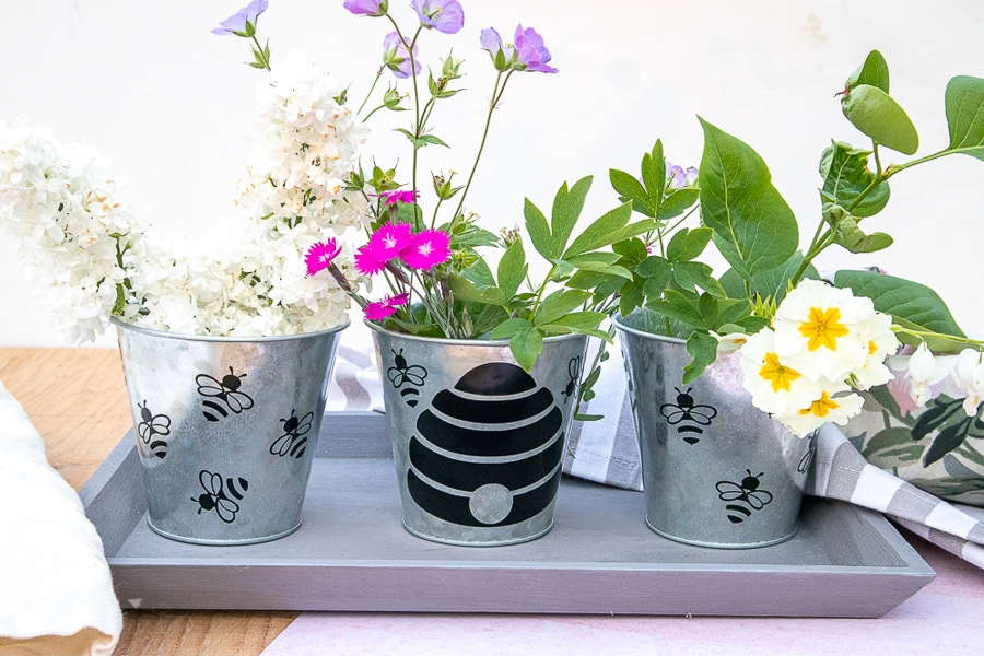 3 custom flower pot crafts with flowers sitting on a tray