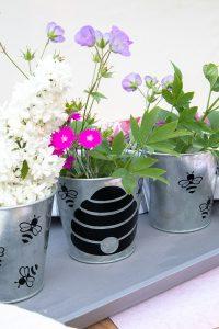 3 custom flower pot crafts with flowers sitting on a shelf