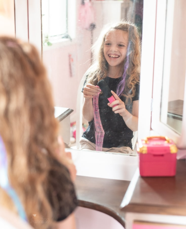 a girl looking in a mirror holding a hair extension