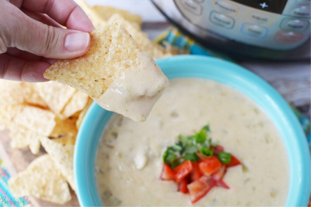 A chip being dipped into Pressure Cooker Queso dip.