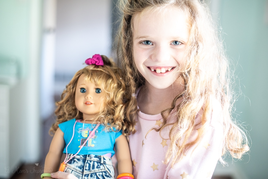 A girl holding am 80's themed doll
