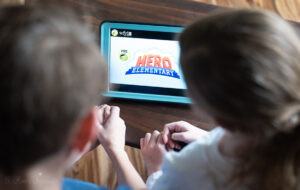 two kids watching hero elementary on an iPad