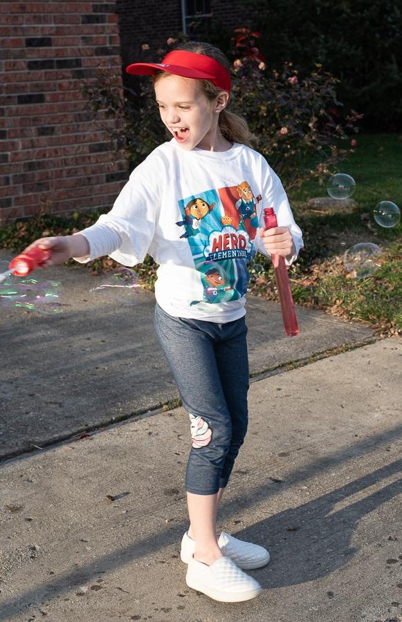 A girl blowing big bubbles