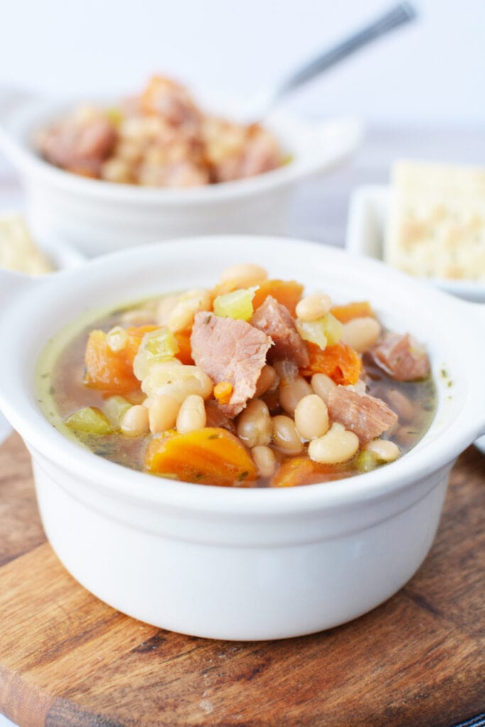 Ham and Bean Soup made in a Pressure Cooker being served in a white bowl.