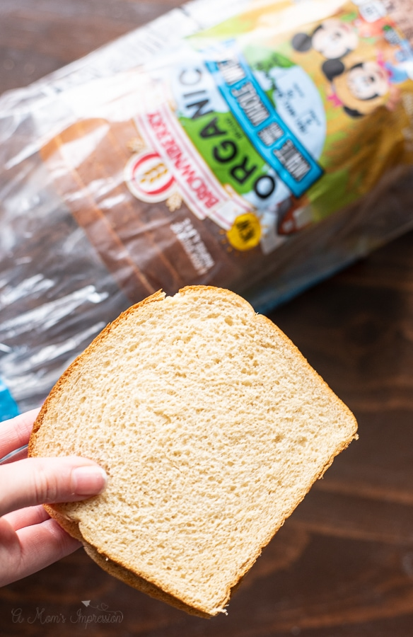 a person holding a piece of wheat bread