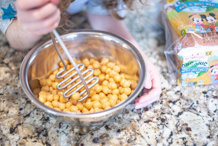 smashing chickpeas with a potato masher