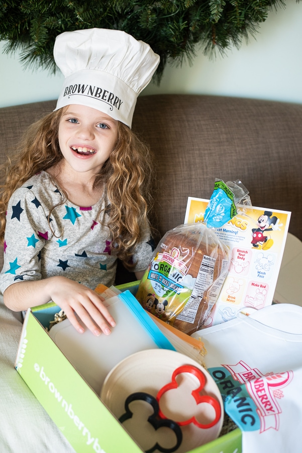 a girl with a box of goodies wearing a chefs hat