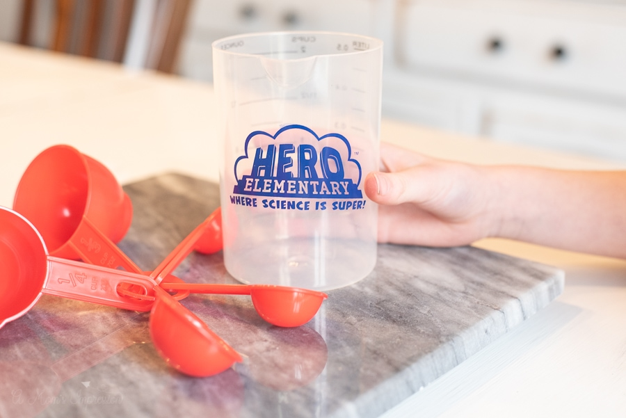 a cup and some measuring spoons with Hero Elementary written on them