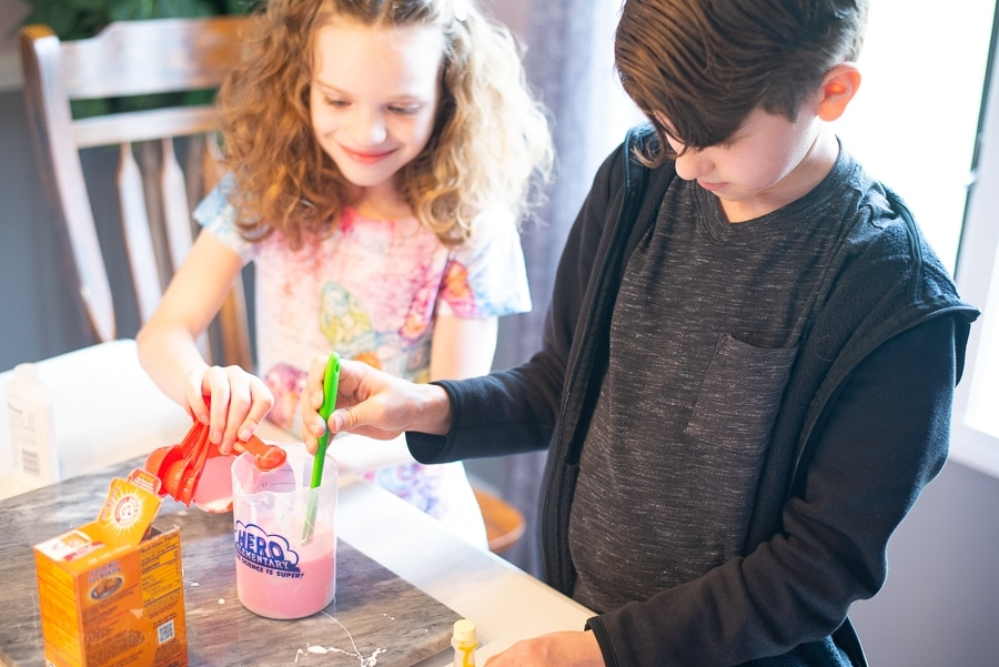 a boy and a girl mixing up glue and water for slime