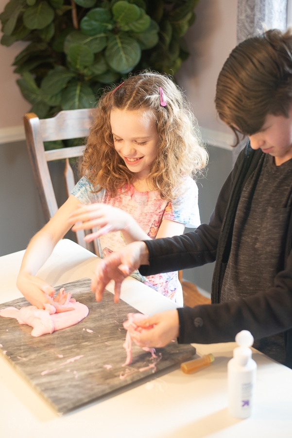 two kids playing with some pink goop on a table