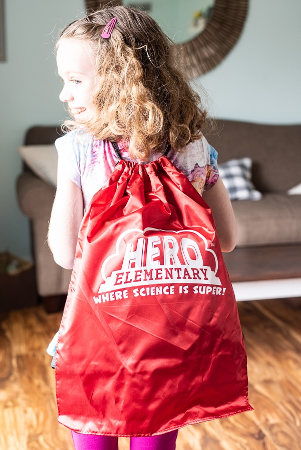 a girl wearing a back pack with Hero Elementary on it