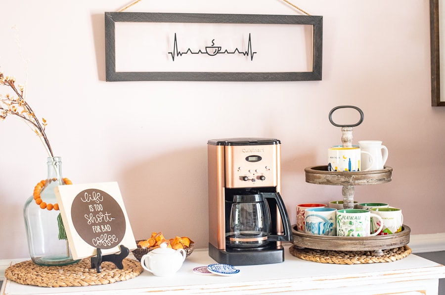 A custom coffee bar set up with coffee mugs, a coffee machine and custom signs