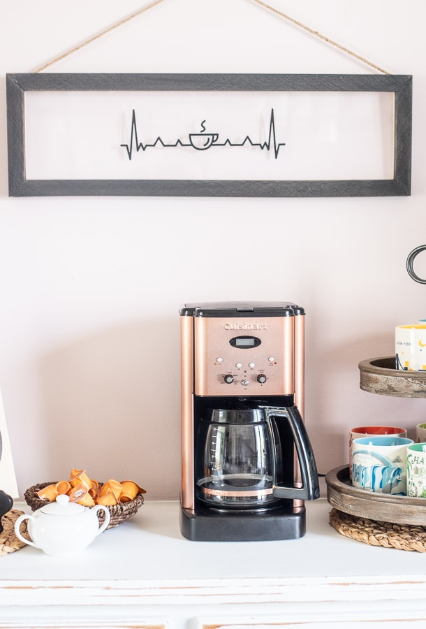A custom coffee bar set up with coffee mugs, a coffe machine and custom signs