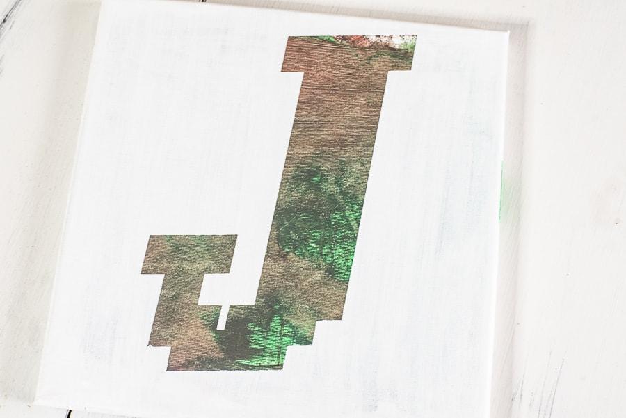 a camo J on a white canvas