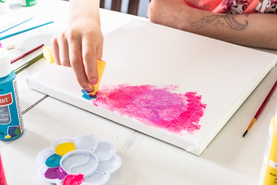 a girl using a foam brush to pain bright pink paint on a canvas