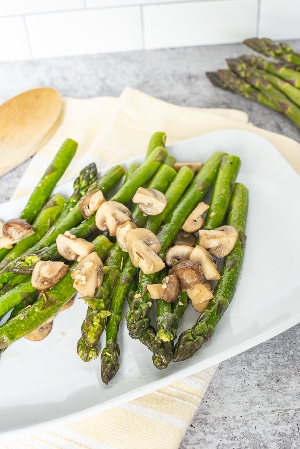 a white platter with asparagus with mushrooms