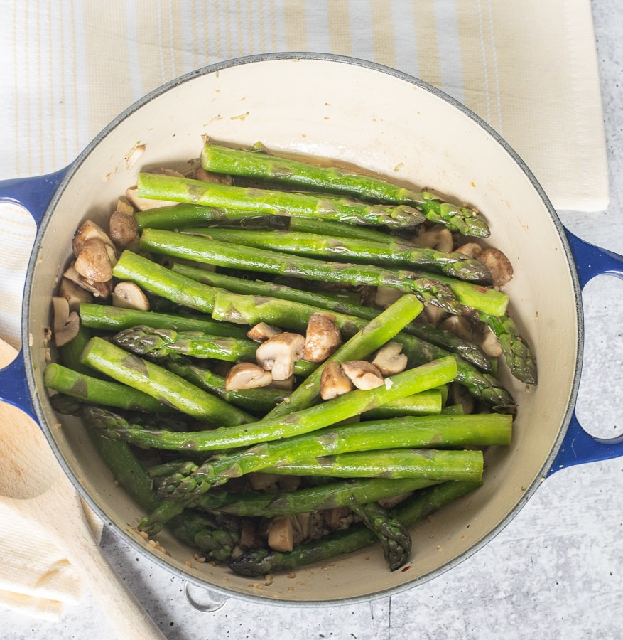 a blue skillet with sauteed asparagus
