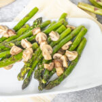 A side of asparagus with mushrooms on a white plate